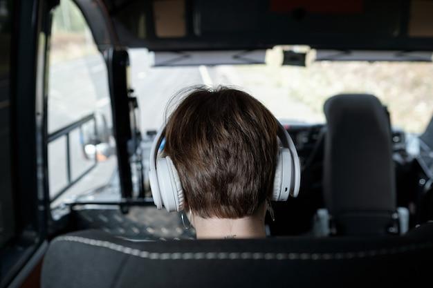 Вид сзади головы девушки в наушниках, путешествующей на автобусе