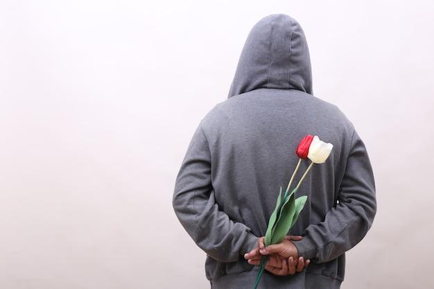 Вид сзади человека с капюшоном, держащего цветы