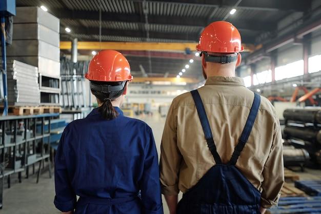 大規模な工場倉庫を考えているオレンジ色のヘルメットの産業労働者の背面図