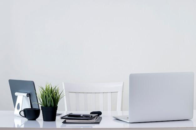 Вид сзади ноутбука и планшета с принадлежностями на белом деревянном столе