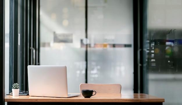コピースペースのあるモダンなオフィスルームの木製テーブルにラップトップコンピューターとコーヒーカップの背面図。