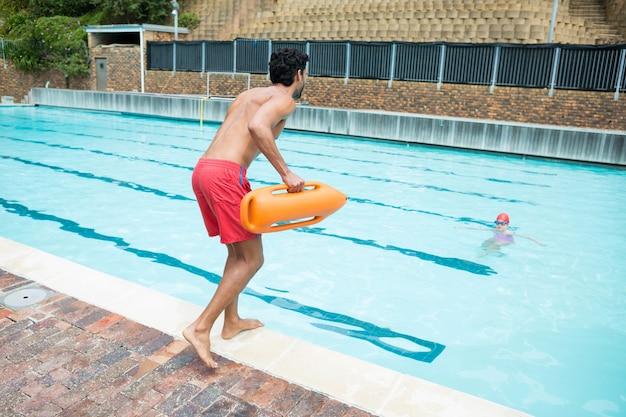 溺れている少年を救助するためにプールに飛び込むライフガードの背面図