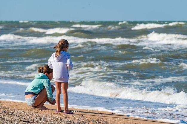 嵐の海の波の近くの砂の上のビーチで遊んでいる小さな子供たちの背面図