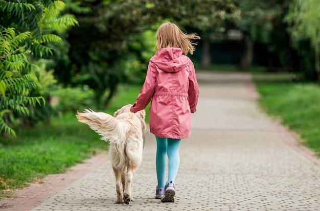 公園内の道路に沿って犬と一緒に歩いている少女の背面図