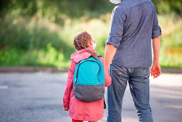 父の手を握ってバックパックを持つ少女の背面図
