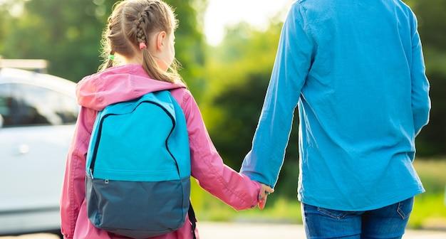 車に行く母親と手をつないでいる小さな女子高生の背面図パノラマオリエンテーション