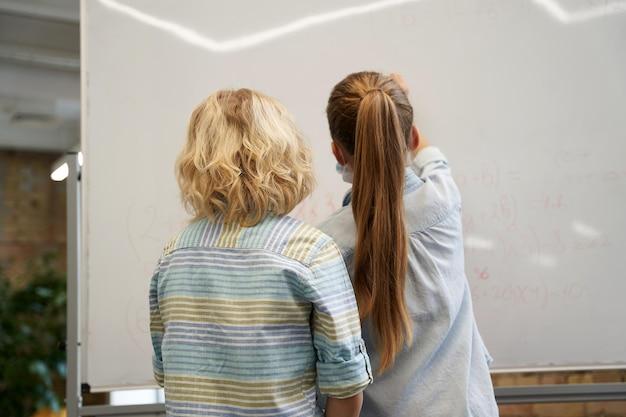 Вид сзади маленьких школьников, мальчик и девочка, пишущие числа на доске в начальной школе