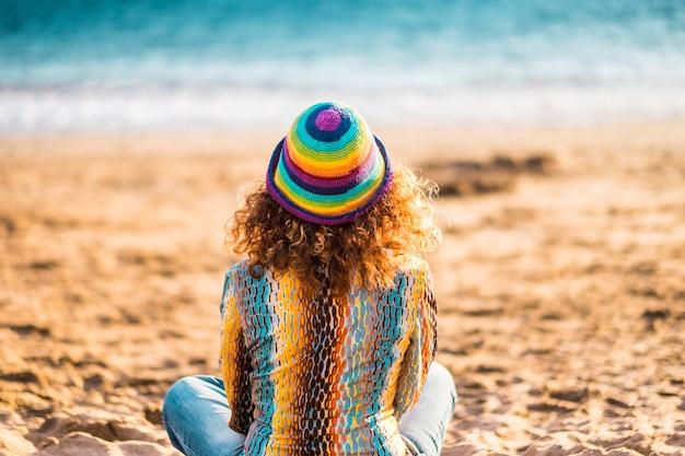 ビーチで砂の上に座っている孤独な女性の背面図。ビーチに座って静かにリラックスする女性。砂の上に座って美しい海の景色を眺める帽子をかぶった女性の背中