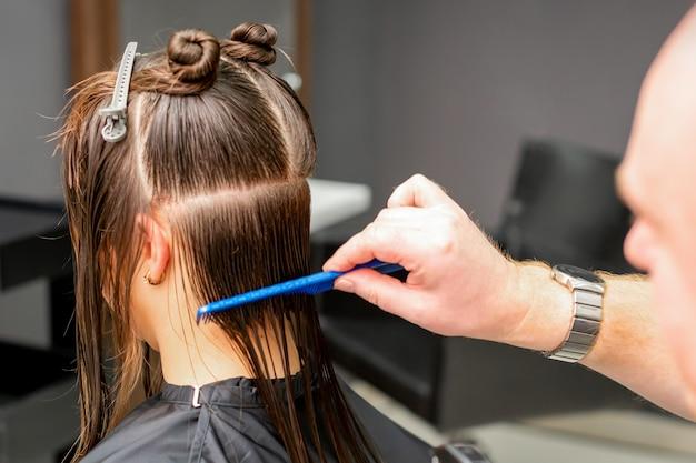 若い白人女性の濡れた髪をとかす男性美容師の背面図は、美容院でセクションに分かれています