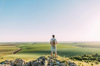 緑色の転がる景色を見ているバックパックで男性の登山者の背面図