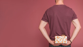 Rear view of man hiding floral gift box against colored background