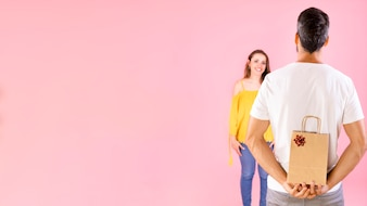 Rear view of man hiding gift from her girlfriend over pink background
