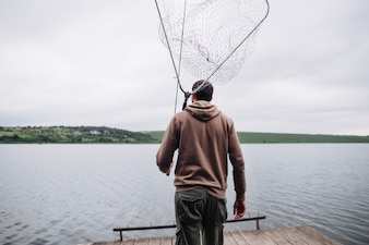 Rear view of man holding fishing net and rod looking at lake