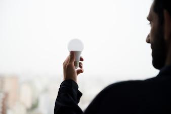 白い電球を握って男の背面図
