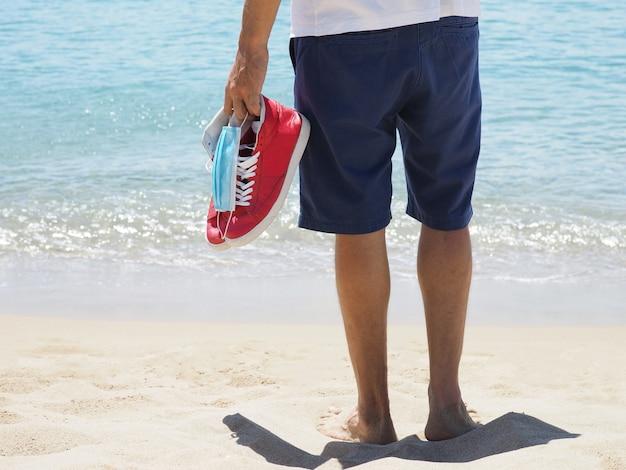 男の後姿はサンディトロピカルビーチで医療マスク、赤いスニーカーを保持しています。