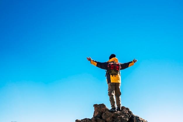 青い空に腕を伸ばして岩の上に立っているバックパックの男の背面図。休暇中に自然を探索する男。青い空に腕を伸ばしてのんきな男のバックパッカーの背面図