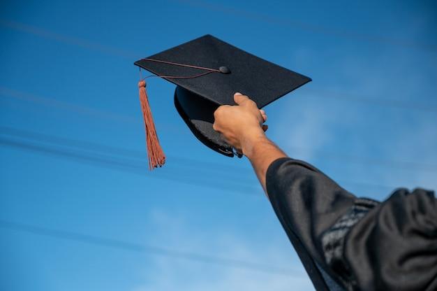 하늘에 대 한 서 있는 모자를 들고 졸업 가운에 남자의 후면 보기