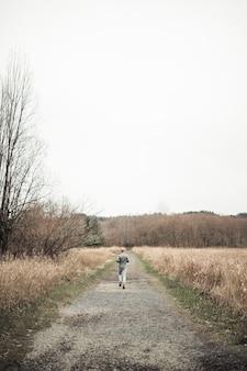フィールドの中の泥の道でジョギングする男のリアビュー