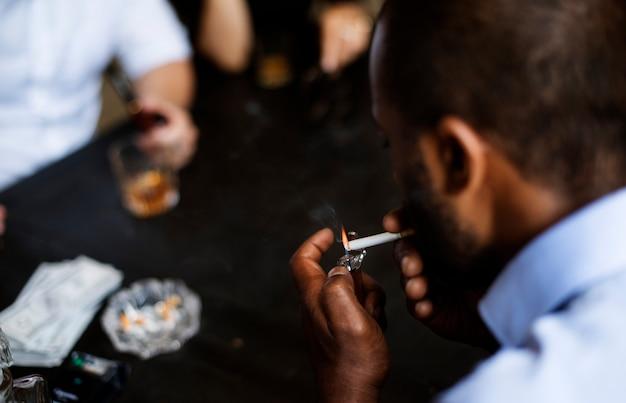 彼の口の中でタバコを照らす男の後ろ姿