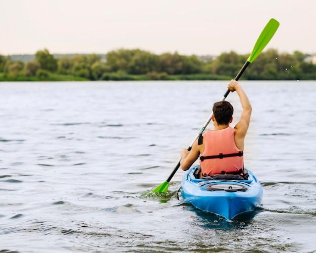 목가적 인 호수에 얕은 얕은 카약 남자의 뒷 모습