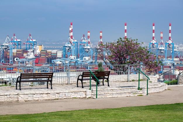 Вид сзади человека, сидящего на скамейке в парке напротив порта хайфа на средиземноморском побережье израиля