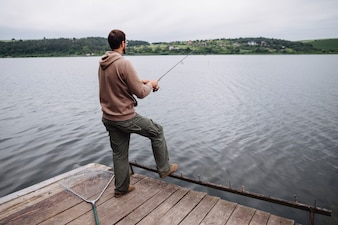 Rear view of man standing on pier fishing in the lake