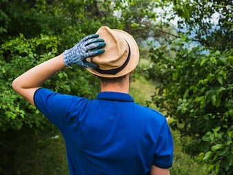 Rear view of man wearing glove touching his hat on head
