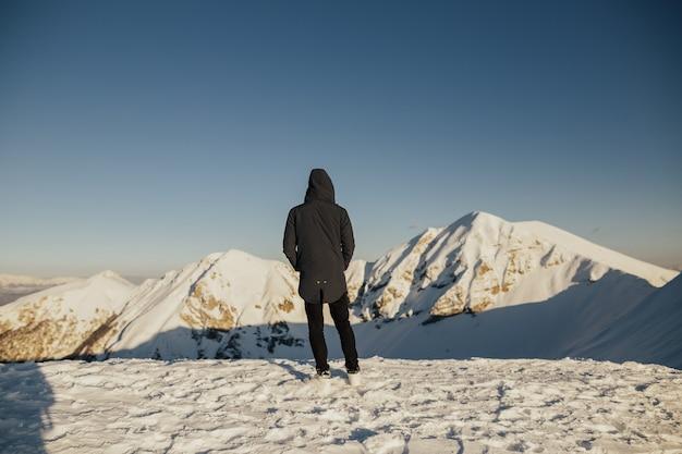 남자의 뒷모습은 눈 덮인 산의 놀라운 자연을 지켜보고 있습니다.