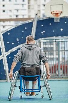 Вид сзади зрелого человека, сидящего в инвалидной коляске и смотрящего на баскетбольную корзину на спортивной площадке