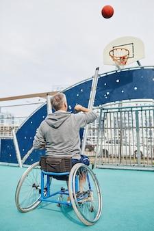 Вид сзади зрелого человека с ограниченными возможностями, сидящего в инвалидной коляске и подбрасывающего мяч в корзину