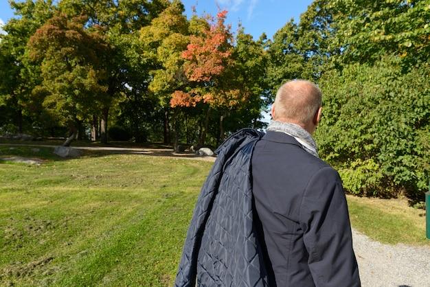 키가 큰 녹색 나무를 향해 잔디 자연 산책로를 걷고 성숙한 스칸디나비아 사람의 후면보기