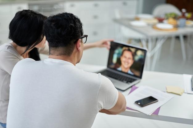 중년 히스패닉 부부, 남녀가 온라인 교육 과정에서 가정에서 랩톱을 사용하여 원격으로 공부하는 동안 교사와 의사 소통하는 후면보기. 성인을 위한 원격 교육