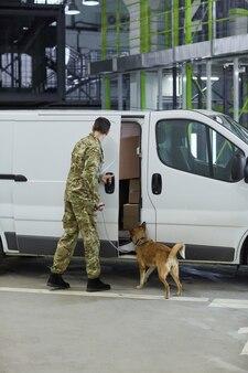 Вид сзади военного с собакой, проверяющей груз в грузовике перед доставкой