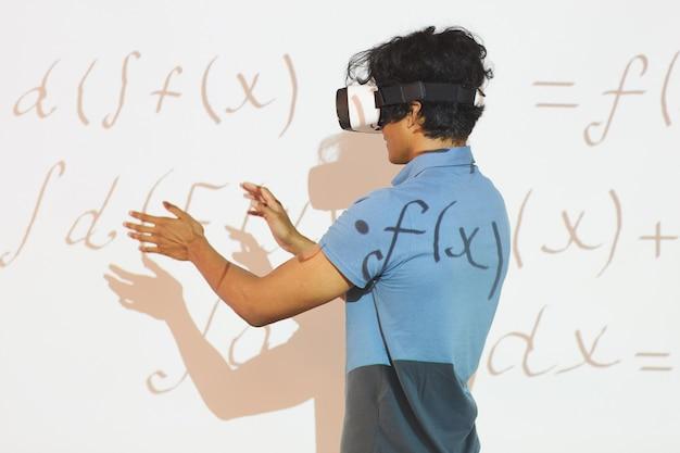 Vr 장치에서 수학 계산을 분석하는 동안 손을 몸짓으로하는 혼혈 학생 소년의 후면보기