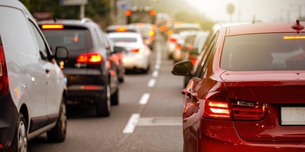 Вид сзади современного автомобиля с включенными стоп-сигналами в час пик