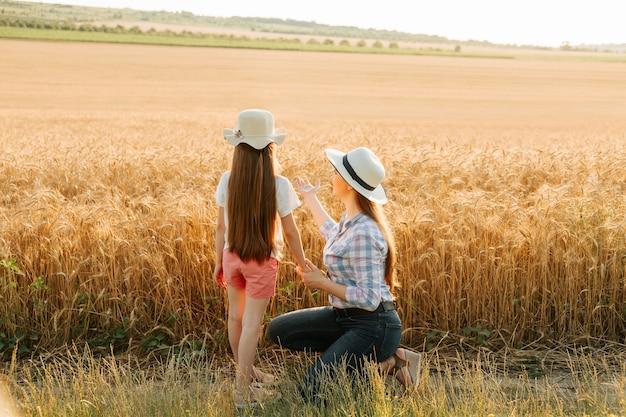 Вид сзади матери и дочери, указывающих на маму пшеничного поля и ее маленькую семью фермеров в шляпе ...