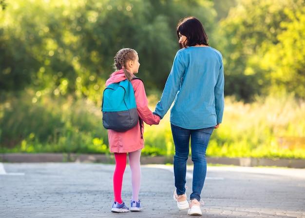 駐車場に沿って歩く手をつないで母と女子高生の背面図