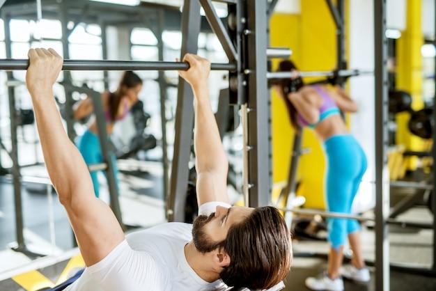Вид сзади мотивированного и сосредоточенного привлекательного бородатого молодого фитнес-человека, делающего упражнения на грудь на тренажере, лежа на наклонной скамье.