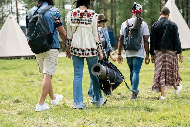 Вид сзади многоэтнических туристов в летних костюмах, идущих по траве к палаткам, планируя остаться в лагере, концепция фестиваля