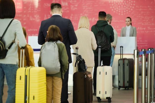 荷物を列に並べて飛行機の出発を待っている人々の背面図