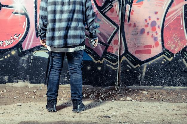 Вид сзади человека, стоящего перед граффити, держащего бутылку с распылителем
