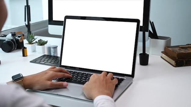 여러 장치로 작업하는 사진 작가 또는 그래픽 디자이너의 후면보기. 그래픽 디스플레이 몽타주를위한 빈 화면.