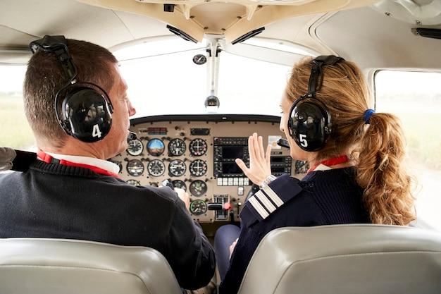 パイロット訓練生とコックピットの女性飛行教官の背面図