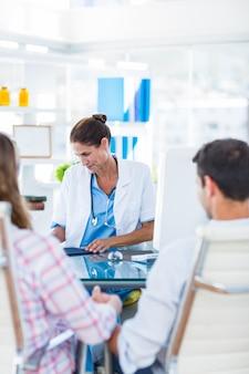 Вид сзади беременная женщина и ее муж обсуждают с врачом