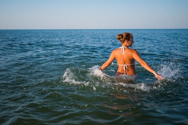 Вид сзади довольно молодая женщина, купание в море