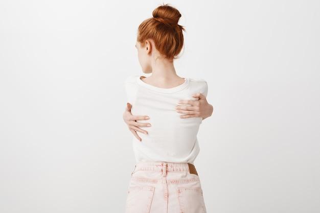 自分を抱いて赤毛の女の子の背面図