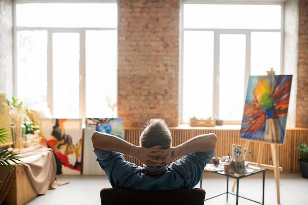 芸術のスタジオで頭の後ろに彼の手で肘掛け椅子に座って落ち着いたプロの画家の背面図