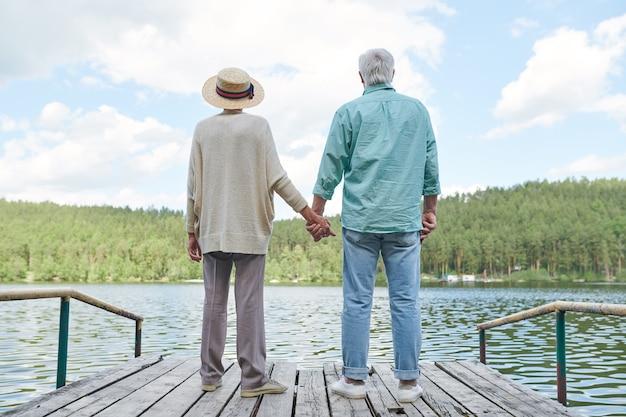 Вид сзади спокойной пожилой пары, наслаждающейся одиночеством на берегу, стоя на деревянном понтоне