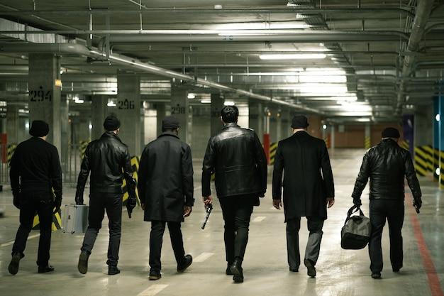Вид сзади на ряд гангстеров с пистолетами и сумками, движущихся вдоль парковки, чтобы встретить кого-то, чтобы передать деньги