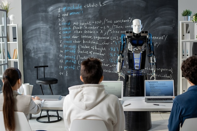 Вид сзади ряда студентов, сидящих за столом перед роботом-автоматом, стоящим у доски вместо учителя-человека